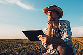 Farmer agronomist with tablet computer in bare empty field