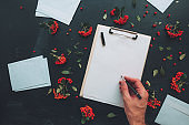 Flat lay hand writing letter on clipboard notepad