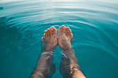 Male feet in outdoor swimming pool