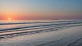 Beautiful colorful vibrant sunrise over low tide beach landscape peaceful scene