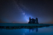 Vibrant Milky Way composite image over landscape of Priory ruins in countryside