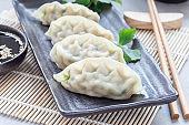 Steamed Korean dumplings Mandu with chicken meat and vegetables on black plate, horizontal