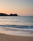 Stunning vibrant sunrise landscape image of Porthcurno beach on South Cornwall coast in England