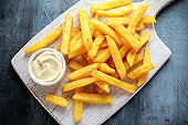 Homemade Baked Potato Fries with Mayonnaise on white wooden board