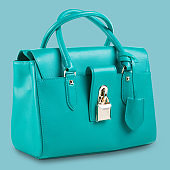 new turquoise women bag on a blue pastel background