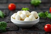 Fresh Italian Mozzarella cheese with cherry tomatoes and basil in white bowl
