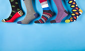 five different men's socks in a row on a pastel blue background, concept