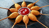 Mini Corn Dogs on black plate with ketchup