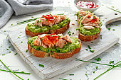 Homemade Toast sandwich with Salmon, Avocado and chilli jam on wihte wooden board. healthy food