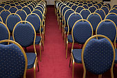 large conference room with red carpet and blue elite seats, comfortable armchairs, many armchairs
