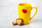 Tea in a yellow mug with a heart and cookies