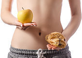 Beautiful young woman holding a bun croissant apple centimeter diet losing weight choise