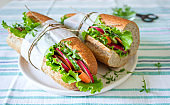 Vegetarian sandwich from bran bread with vegetables and herbs for a picnic. Rustic style.