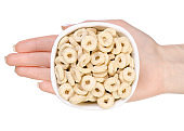 Breakfast cereal rings in a bowl in a hand