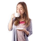 Young beautiful woman in a bathrobe with a cup of tea coffee