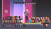 Fashion model man walking over catwalk stage runway podium in showing new collection fashionable suit. Audience crowd sitting and watching exhibition show. Flat style isolated vector