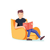 Caucasian white man relaxing with a book on the armchair. Young clever student drinking coffee and reading a novel at home.