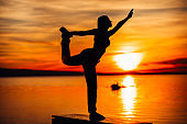 Carefree woman meditating in nature.Finding inner peace.Yoga practice.Spiritual healing lifestyle.Enjoying peace,anti-stress therapy,mindfulness meditation.Positive energy.King dancer,mountain pose