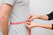 Woman's hands measuring young, slim man's waist with pink measuring tape. Part of body on gray background. Right size. Closeup. Side view.
