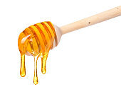 Rich honey dripping from wooden dipper spoon