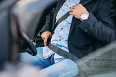 Bearded senior adult businessman fastening seat belt in his car.