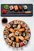 sushi rolls Asian food on round slate black Board with wasabi and ginger, soy sauce on white background