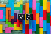Letters VS on colorful wooden background with copy space. The concept of making choice.  Black cubes with letters VS.