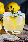 Lemon cocktail on dark rustic background, close-up. Refreshing alcoholic yellow cocktail drink.