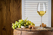 Wine bottle, glass of white wine and bunch of grapes on a old wooden barrel.