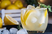 Lemon cocktail with thyme and ice on dark rustic background, close-up. Refreshing alcoholic yellow cocktail drink.
