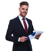portrait of young businessman checking his files and smiling