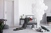 Bunch of white balloons next to single metal bed with grey bedding and white and dark red pillows in bright scandinavian bedroom interior, real photo