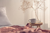 Closeup of coffee cup and flower in glass vase on the bedside table of bright bedroom interior, real photo with copy space on the empty wall