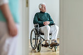 Sad disabled elderly man in the wheelchair in the hospital. Blurred nurse in a foreground