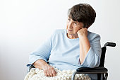 Sad disabled senior woman on the wheelchair against white background