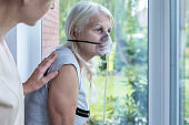 Nurse supporting sick senior woman with oxygen mask in the hospital