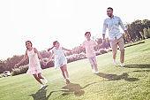 Bonding. Family of four running on grassy field smiling cheerful