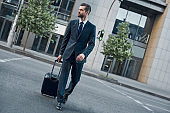 Young businessman with a suitcase on wheels walks on the empty road