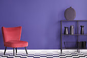 Real photo of a colorful living room interior with red, velvet armchair and black rack with decorations against an ultra violet wall