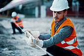 Worker in orange uniform and white helmet. Safety during roadworks