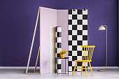Yellow chair and plant against pastel pink wall with checkered fabric in violet room interior. Real photo