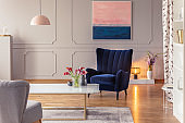 Real photo of a romantic living room interior with an armchair, painting, cozy light and flowers
