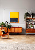 Orange painting above wooden cupboard in retro flat interior with armchair and plants. Real photo