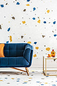 Blue sofa with orange pillow next to table in colorful living room interior with wallpaper. Real photo