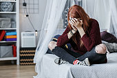 Rebellious girl crying on bed