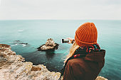 Woman taking photo by smartphone of sea landscape Travel Lifestyle concept adventure vacations outdoor