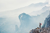 Traveler hiker on cliff traveling with backpack Travel Lifestyle concept adventure active vacations outdoor rocky mountains Landscape aerial view on background