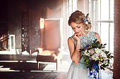 Young beautiful woman in wedding dress with bouquet of flowers. Wedding hairstyle, flowers in hair.