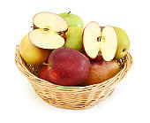 Apples and pears in a straw basket isolated on white background