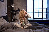 Charming Young woman in pajamas, sitting in bed and drinking morning coffee